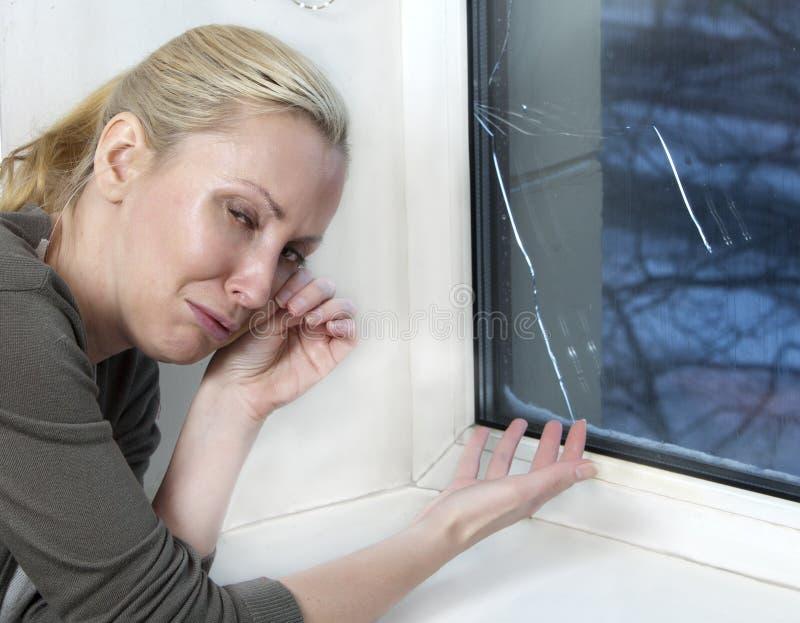 Hemmafrun gråter, det dåliga kvalitets- fönstret har brustit på grund av kallt väder arkivbild
