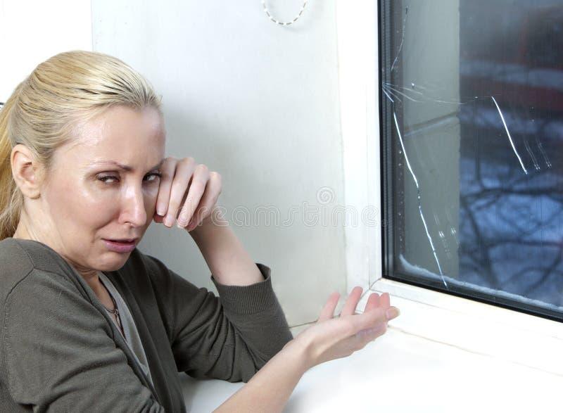 Hemmafrun gråter, det dåliga kvalitets- fönstret har brustit på grund av kallt väder arkivfoto