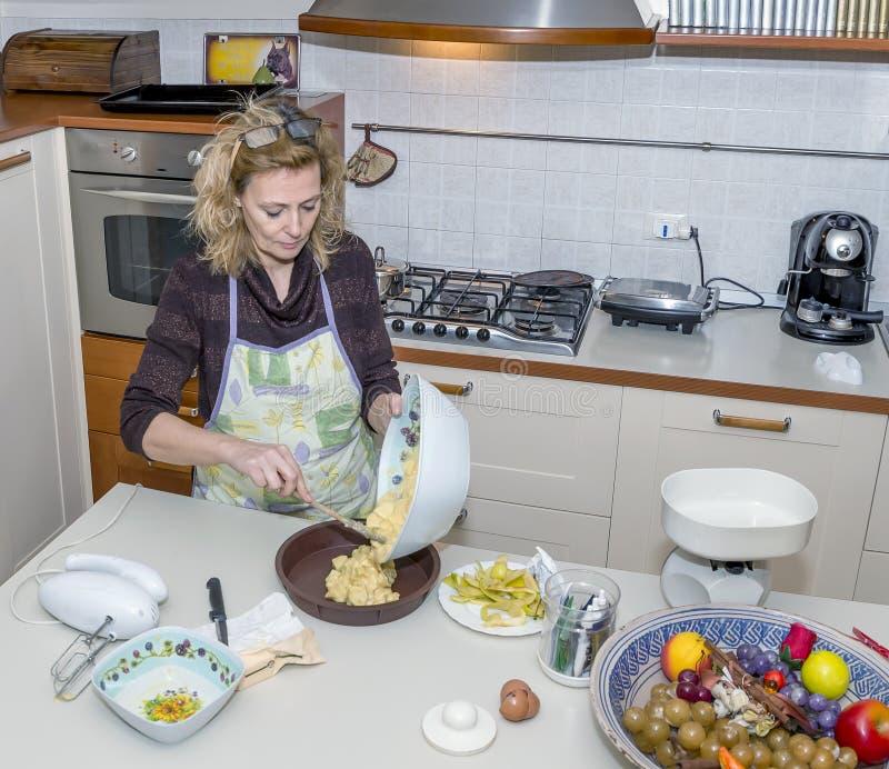 Hemmafrun häller degen in i formen för att förbereda en kaka i ett smutsigt kök royaltyfria bilder