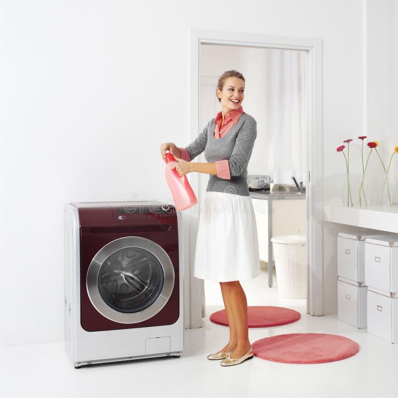 Hemmafrun håller tvättmedel royaltyfri bild