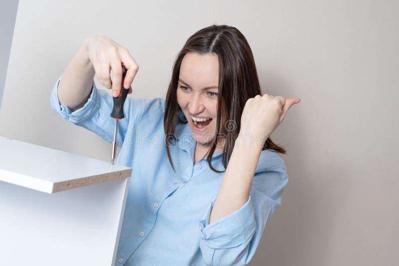 Hemmafrun i blå skjorta med skruvmejsel vrider skruven, tycker om lyckat arbete arkivbilder