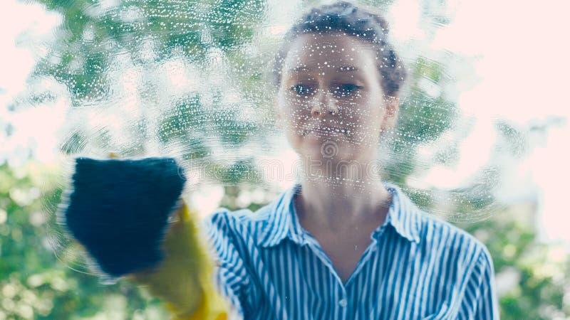 Hemmafrun i skjorta torkar fönsterexponeringsglas med den blåa våta trasan arkivbilder