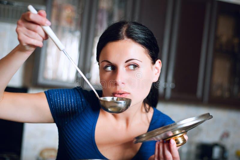 Hemmafrun lagar mat mat i kök fotografering för bildbyråer