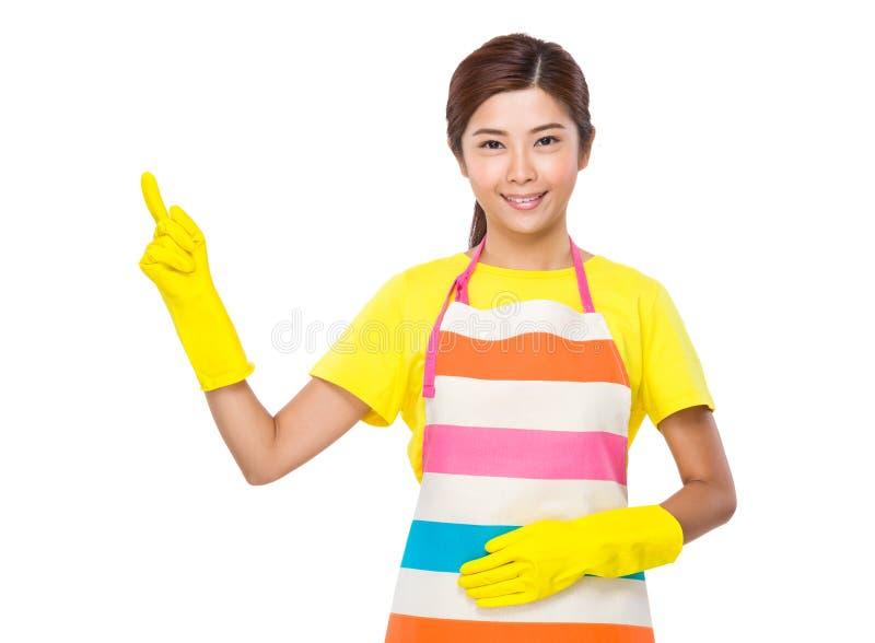 Hemmafrun med plast- handskar och fingret pekar upp arkivfoton