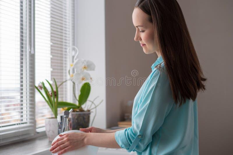 Hemmafrun tvättar disk framme av fönstret i köket, i det mjuka ljuset av morgonen fotografering för bildbyråer