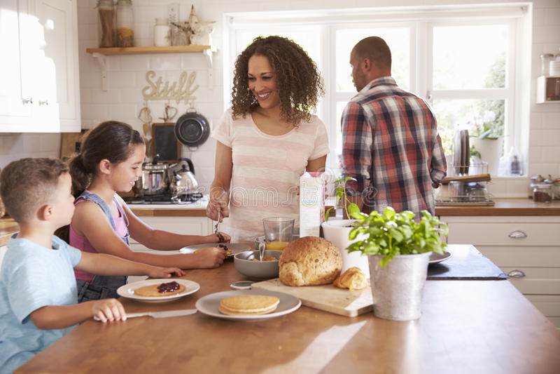 Hemmastadd ätafrukost för familj i kök tillsammans royaltyfri fotografi