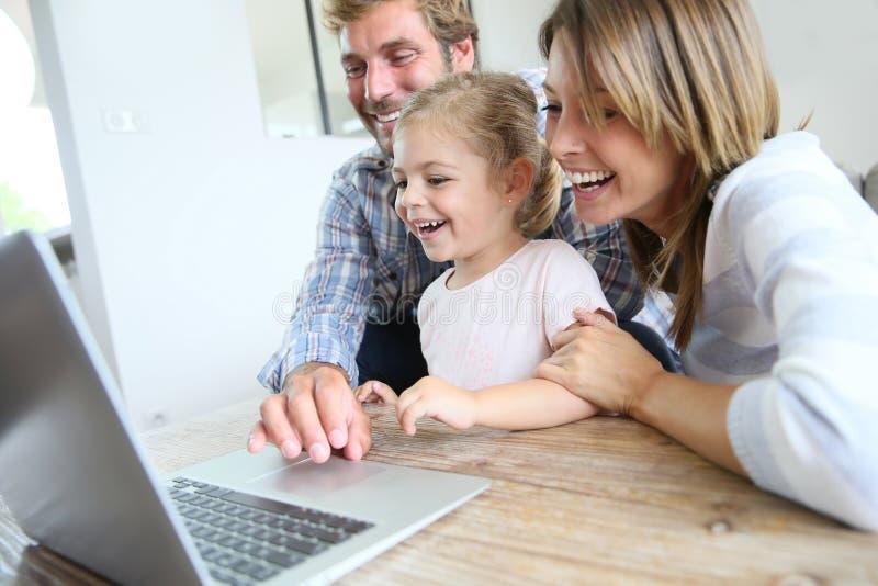 Hemmastadd användande bärbar dator för lycklig ung familj royaltyfria bilder