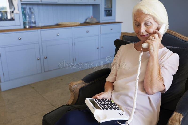 Hemmastadd användande telefon för hög kvinna med Over storleksanpassade tangenter arkivbilder