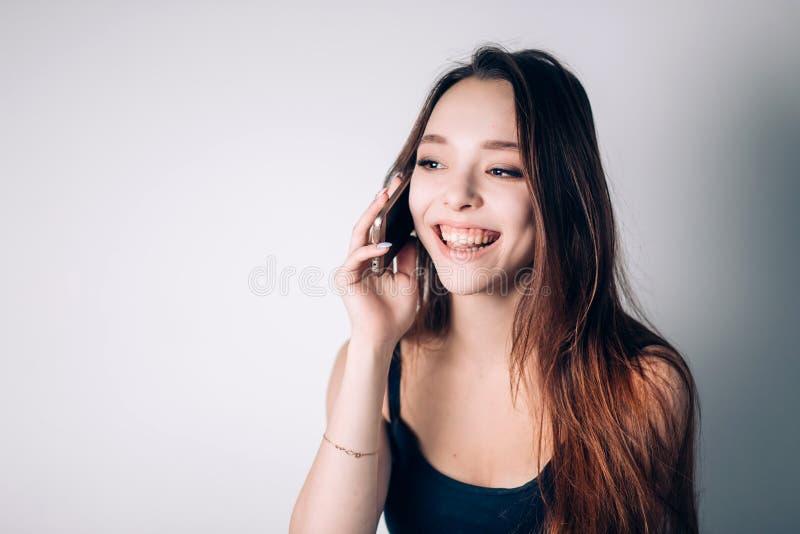 Hemmastadd flicka som kallar på telefonen Den lyckliga kvinnan använder en smartphone royaltyfria foton