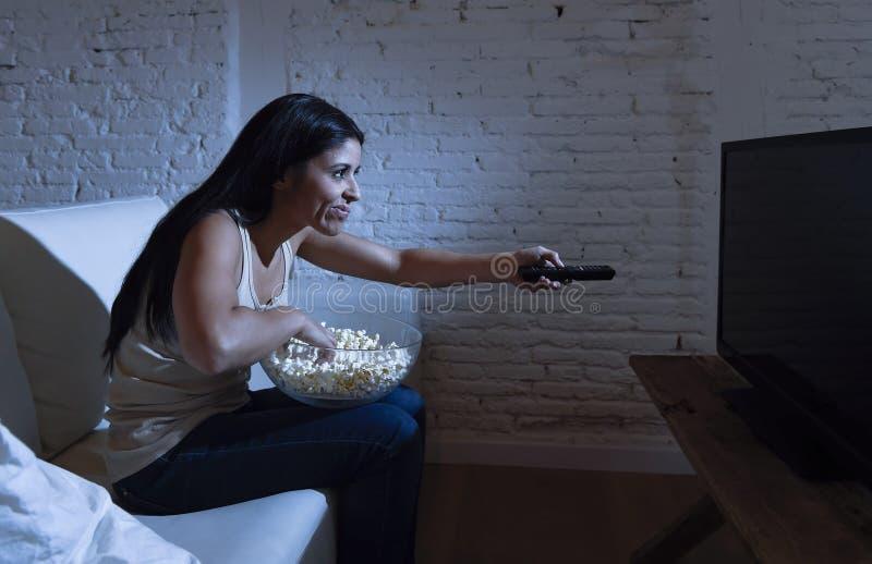 Hemmastadd hållande ögonen på television för ung härlig latinamerikansk kvinna som är ilsken och som är uppriven om tvprogram arkivbilder