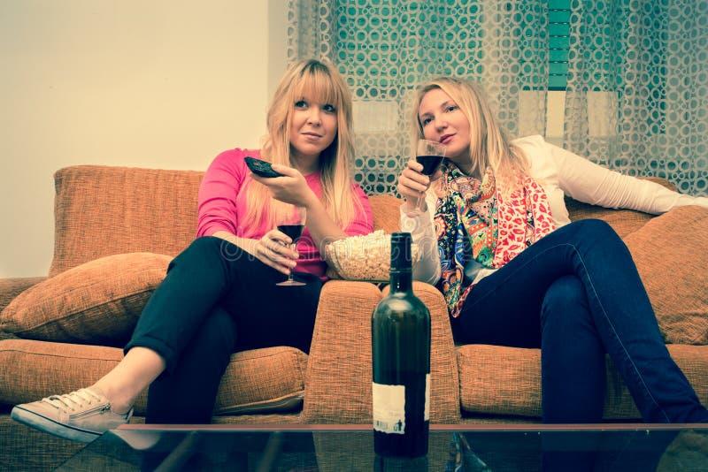 hemmastadd hållande ögonen på tv för 2 kvinnliga vänner och dricka filtrerad bild för vin retro stil royaltyfri bild