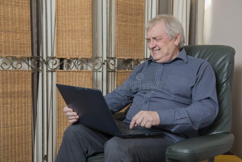 Hemmastadd lycklig mogen man se en bärbar dator royaltyfri bild