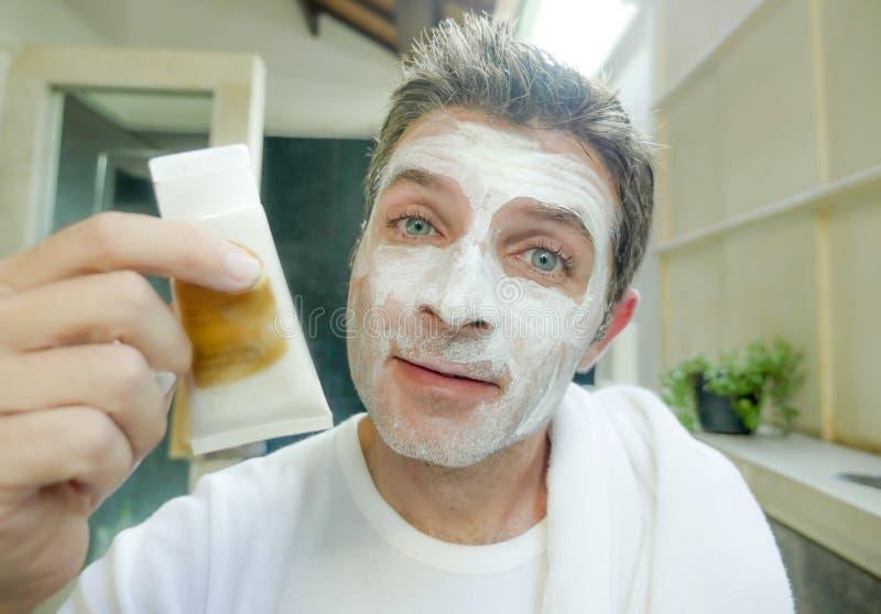 Hemmastadd lycklig och attraktiv Caucasian man se honom på badrumspegeln som applicerar vit facemask i den manliga skönhet och an royaltyfria bilder