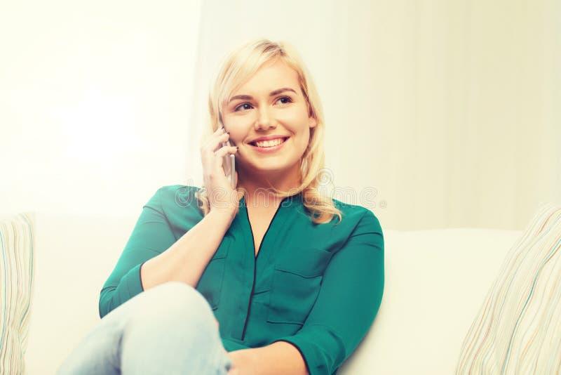 Hemmastadd lycklig ung kvinna som kallar på smartphonen royaltyfria bilder