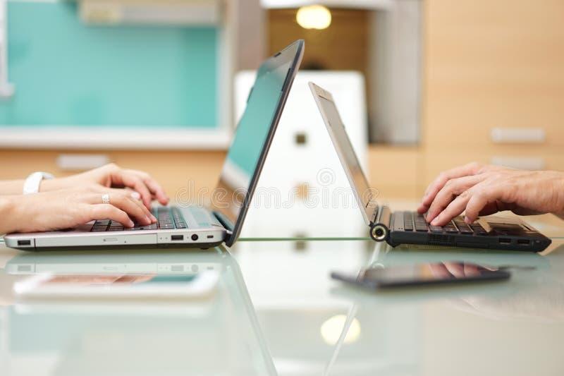 Hemmastadd maskinskrivning för kvinna och för man på bärbar datordatoren royaltyfria foton