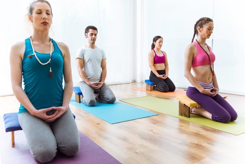 Hemmastadd praktiserande yoga för grupp människor Vajrasana poserar arkivbild