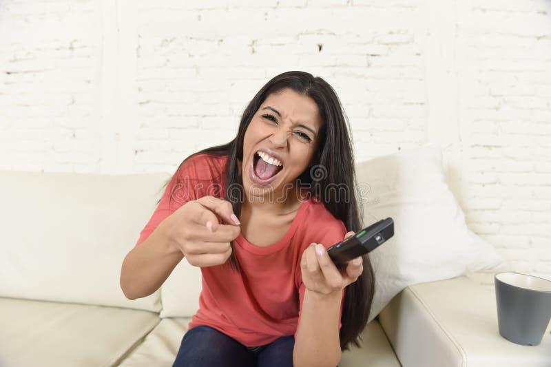 Hemmastadd soffasoffa för attraktiv latinsk kvinna som skrattar och ler lycklig hållande ögonen på television arkivfoto