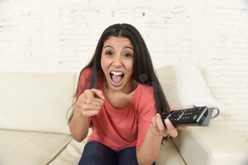 Hemmastadd soffasoffa för attraktiv latinsk kvinna som skrattar och ler lycklig hållande ögonen på television fotografering för bildbyråer