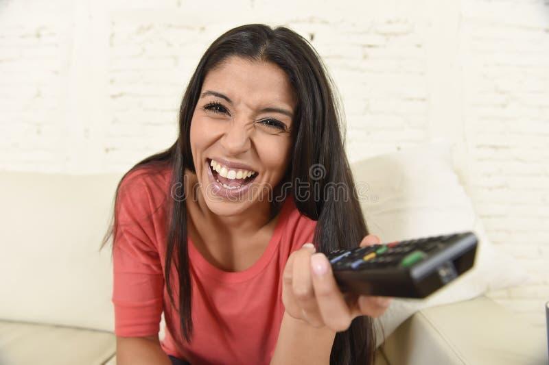 Hemmastadd soffasoffa för attraktiv latinsk kvinna som skrattar och ler lycklig hållande ögonen på television arkivbilder
