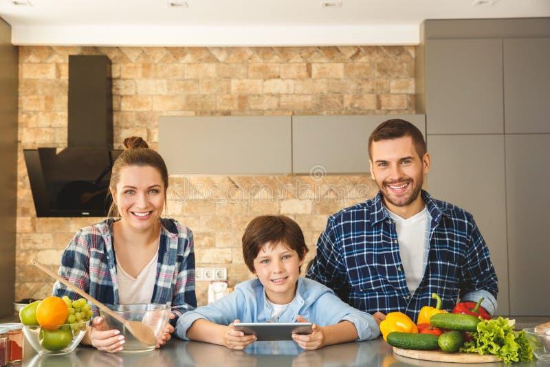 Hemmastatt anseende för familj i kök som ser tillsammans den lyckliga sonen för kamera som rymmer den digitala minnestavlan fotografering för bildbyråer