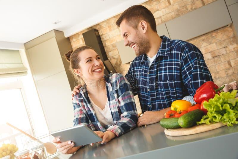 Hemmastatt anseende för unga par i för kök som maken tillsammans kramar frun som använder den digitala minnestavlan som ser de fotografering för bildbyråer