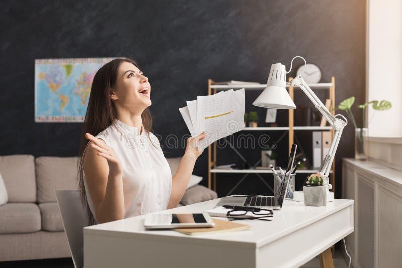 Hemmastatt arbete för lycklig kvinna på bärbar dator- och läsningdokument fotografering för bildbyråer