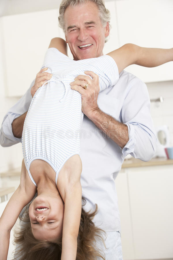Hemmastatt för hållande sondotter för farfar uppochnervänt arkivfoto