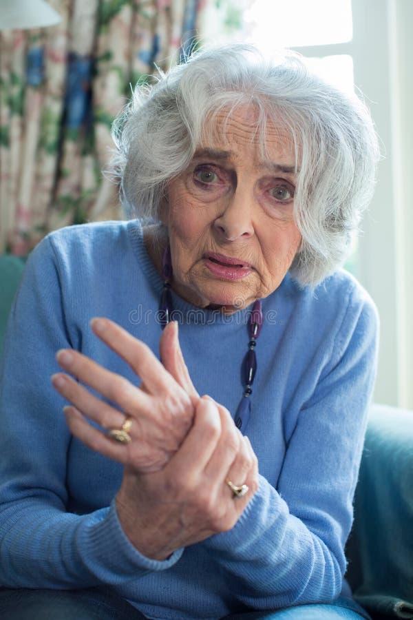 Hemmastatt lidande för hög kvinna med artrit royaltyfri fotografi