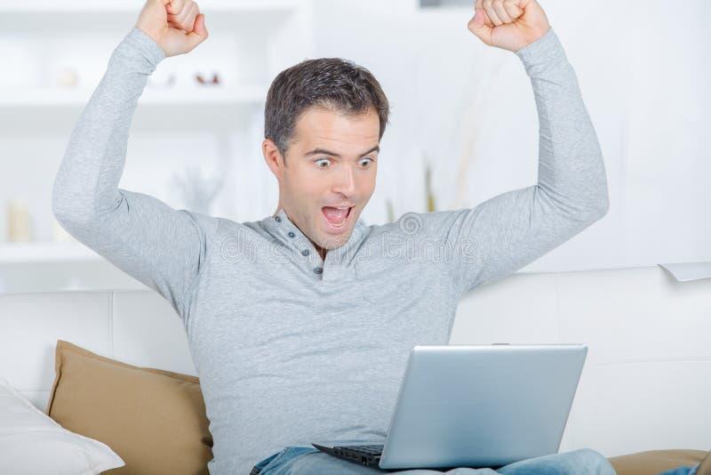 Hemmastatt manligt arbete för lyckligt arbete på att le för bärbar dator royaltyfria foton