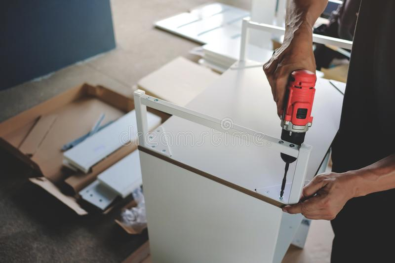 Hemmastatt monterande möblemang Flytta sig för ett nytt hus eller DIY-begrepp Hantverkare som använder den sladdlösa skruvmejseln arkivfoton