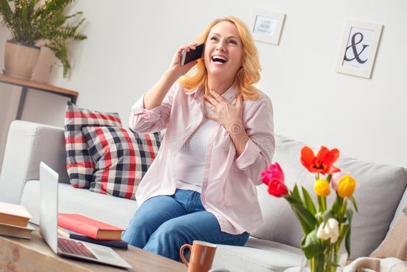 Hemmastatt sammanträde för hög kvinna som talar på den glade smartphonen royaltyfri bild