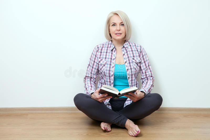Hemmastatt sammanträde för kvinna på den golvatt koppla av och läseboken arkivfoton