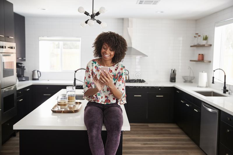 Hemmastatt sammanträde för kvinna på stund för kökö genom att använda mobiltelefonen royaltyfri foto