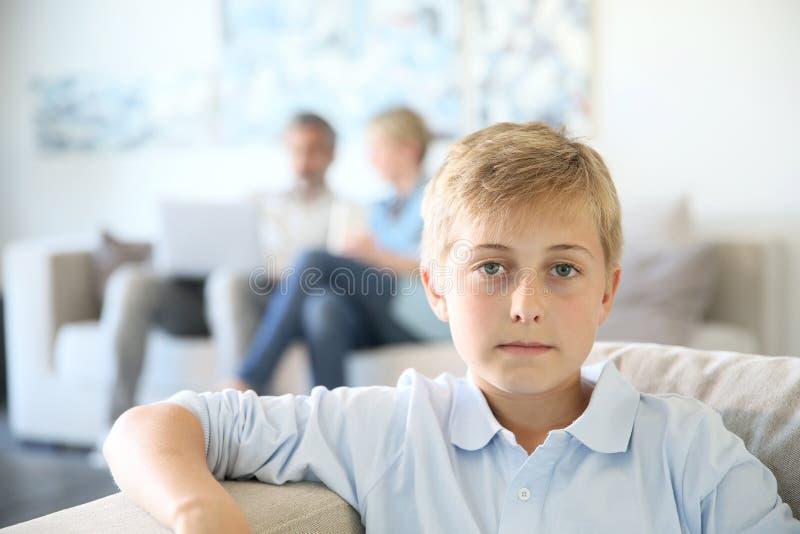 Hemmastatt sammanträde för tonåringpojke på soffan arkivfoton