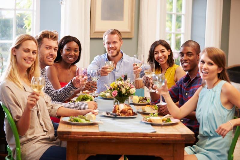 Hemmastatt sammanträde för vänner runt om tabellen för matställeparti arkivbild