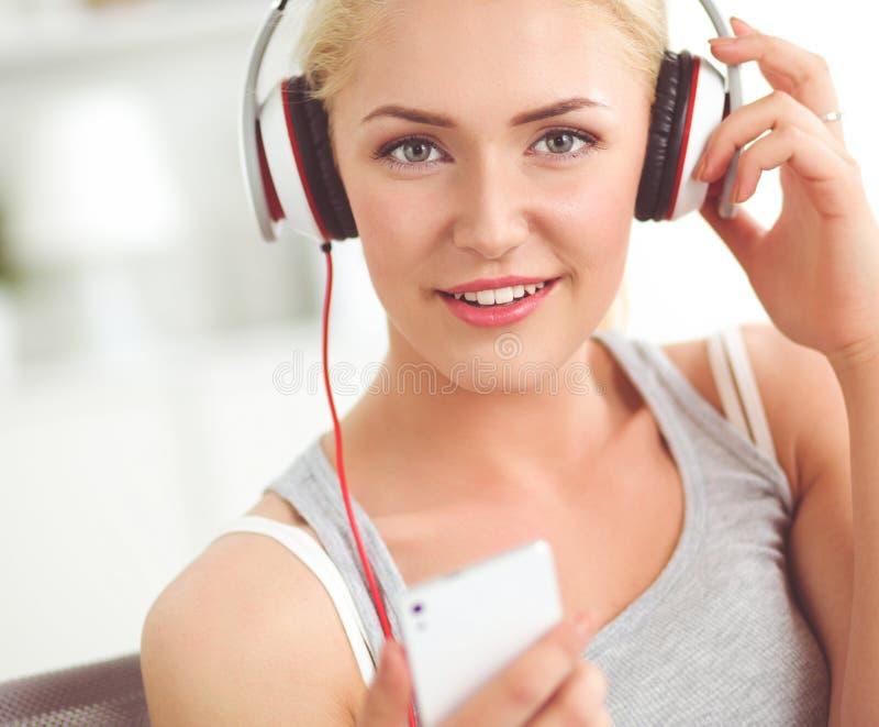 Hemmastatt sammantr?de f?r ung h?rlig kvinna p? soffan och lyssnande musik arkivbild