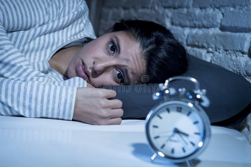 Hemmastatt sovrum för latinamerikansk kvinna som sent ligger i säng på natten som försöker att sova lidandesömnlöshet arkivbilder