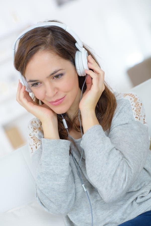 Hemmastatt tyckande om lyssna för kvinna till ljudsignal på hörlurar royaltyfria bilder