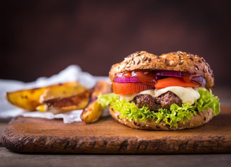 Hemmet gjorde hamburgaren med gr?n sallad och med amerikanska potatisar bakom brunt tr? f?r bakgrund arkivfoton
