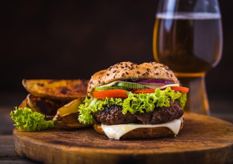 Hemmet gjorde hamburgaren med ost och gr?n sallad och med amerikanska potatisar in bakom naturligt tr? f?r bakgrund royaltyfri foto