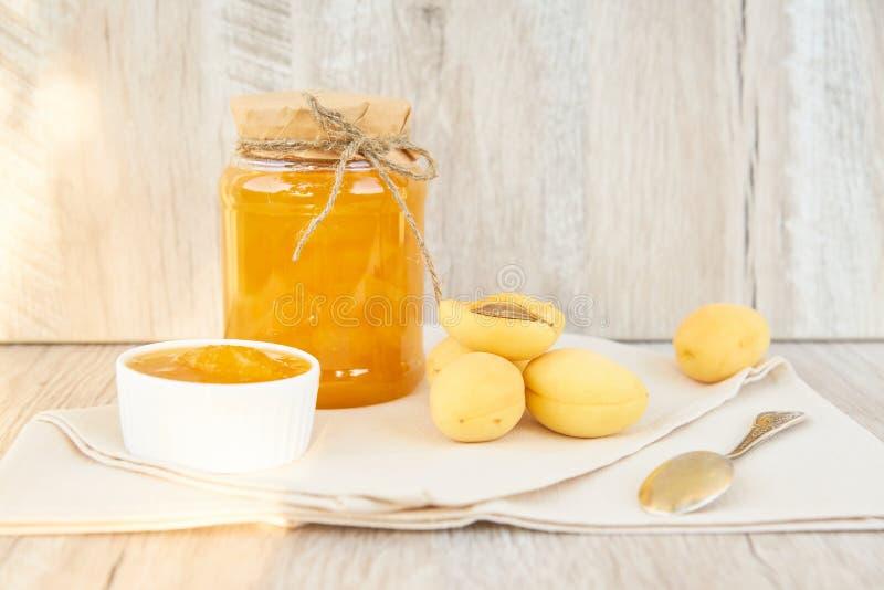 Hemmet gjorde organiskt aprikosdriftstopp i exponeringsglaskrus och mogna aprikors på den trälantliga tabellen fotografering för bildbyråer