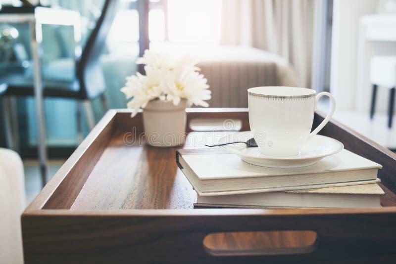 Hemmiljö med blomman för bok för kaffekopp den vita på magasintabellen royaltyfri bild