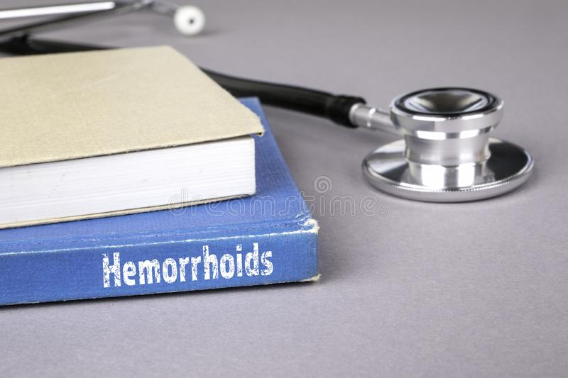 Hemorrhoids. Blue book on a gray office table. Communication and information royalty free stock photography
