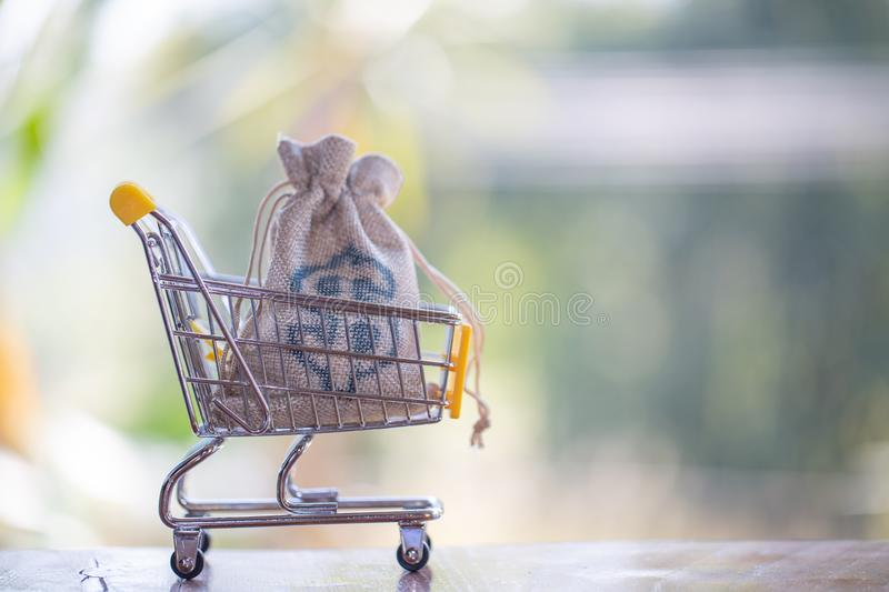 Hemp bag with silver in shopping cart, concept pay spend saving money, supermarket store, Finance and money stock photography