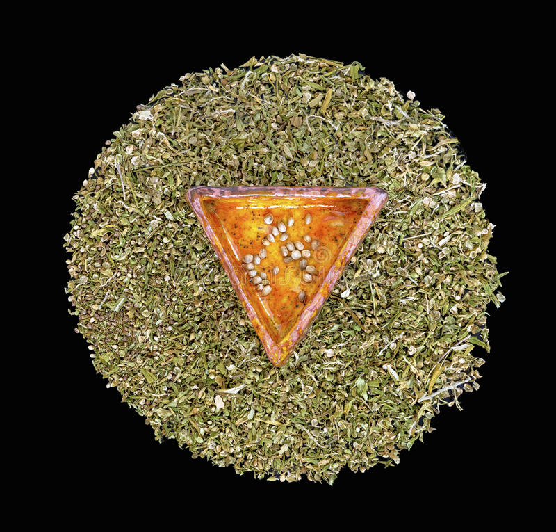 Hemp seeds in a triangular ceramic piece. On a circle of dried hemp leaves in a black background stock photography