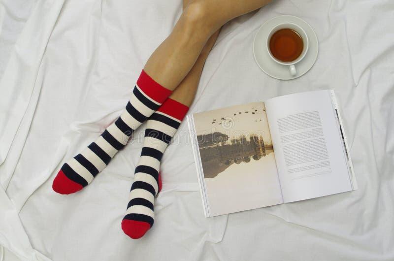 Hemtrevlig afton med en bok och ett te arkivbild