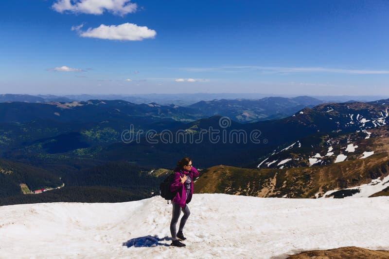 hemtrevlig flicka på berget på snö arkivfoto