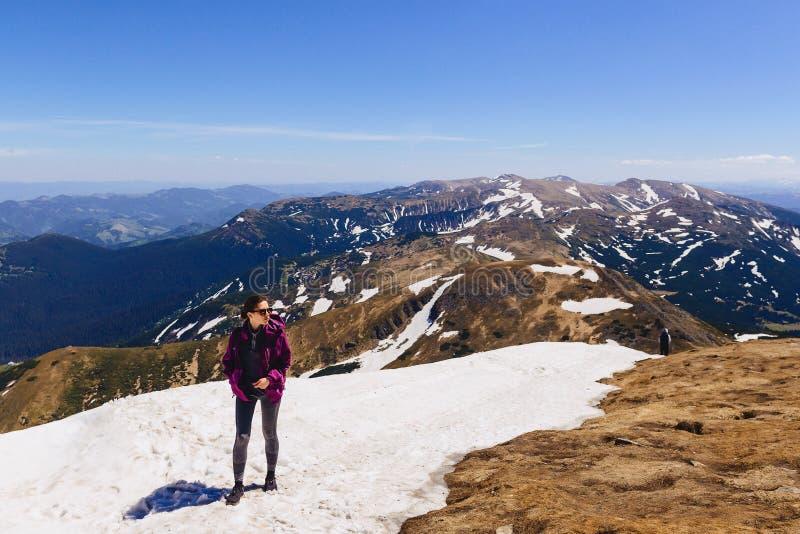 hemtrevlig flicka på berget på snö royaltyfria bilder