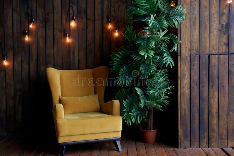 Hemtrevlig gammal senap-färgad fåtölj, palmträd och träväggar inre retro stil Varmt gult girlandljus arkivfoto