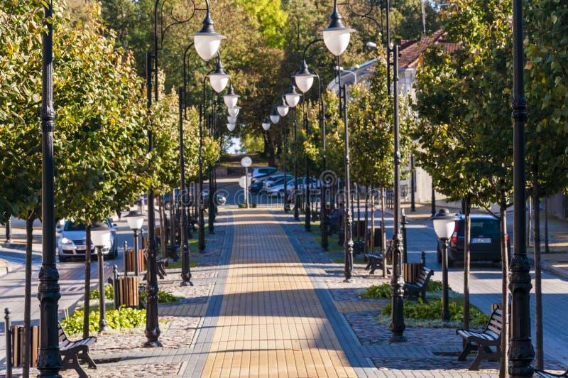 Hemtrevlig gammal stadgränd med rader av lyktor och bänkar royaltyfri fotografi
